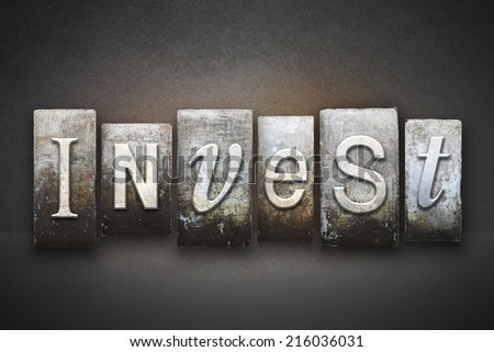 The word INVEST written in vintage letterpress type - stock photo