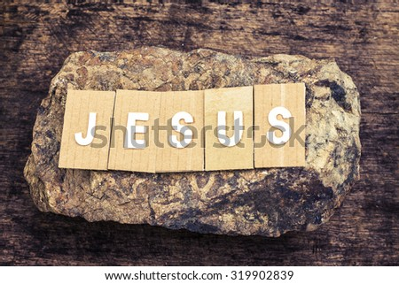 "the word "" Jesus "" design by white letterpress  over the stone on wooden background - stock photo"