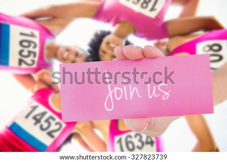 The word join us and young woman holding blank card against five smiling runners supporting breast cancer marathon - stock photo