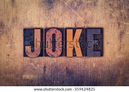 "The word ""Joke"" written in dirty vintage letterpress type on a aged wooden background. - stock photo"