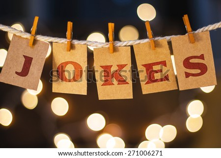 The word JOKES printed on clothespin clipped cards in front of defocused glowing lights. - stock photo