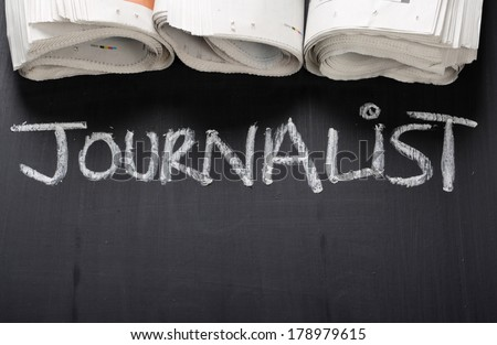 The word Journalist written on a blackboard next to rolled up newspapers, with copy space - stock photo