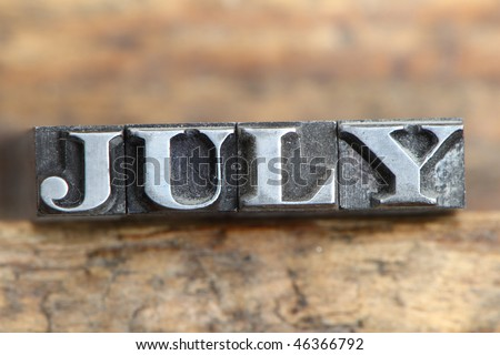 the word july in letterpress type on a wooden background. - stock photo