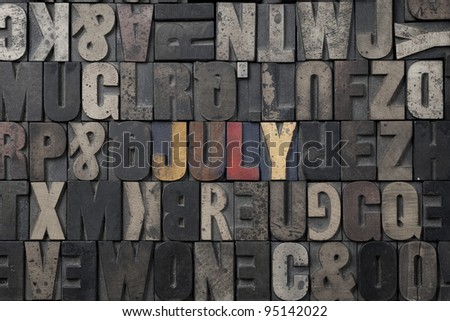 The word July written in antique letterpress printing blocks. - stock photo