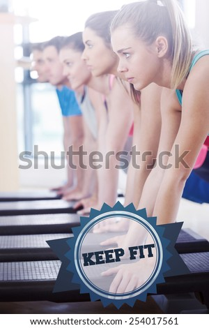 The word keep fit and instructor with fitness class performing step aerobics exercise against badge - stock photo