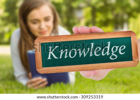 The word knowledge and hand showing chalkboard against university student lying and using tablet pc - stock photo