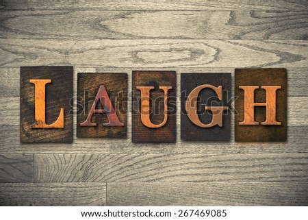 """The word """"LAUGH"""" theme written in vintage, ink stained, wooden letterpress type on a wood grained background. - stock photo"""