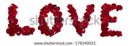 The word love is written with rose petals on a white background. - stock photo