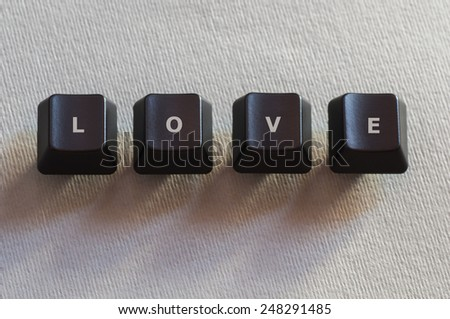 The word Love made of four black computer keyboard buttons - stock photo