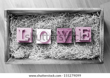 The word Love spelled out in big block letters in a wooden gift box filled with raffia - stock photo