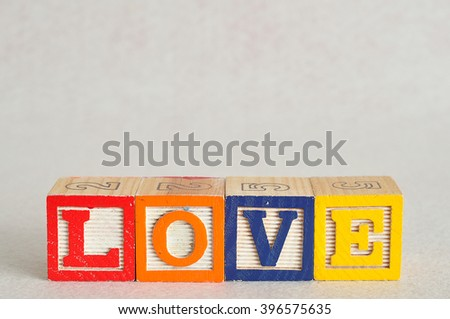 The word love spelled with colorful alphabet blocks isolated on white background - stock photo