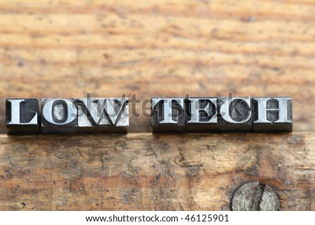"""the word """"low tech"""" in letterpress type on a wooden background. - stock photo"""