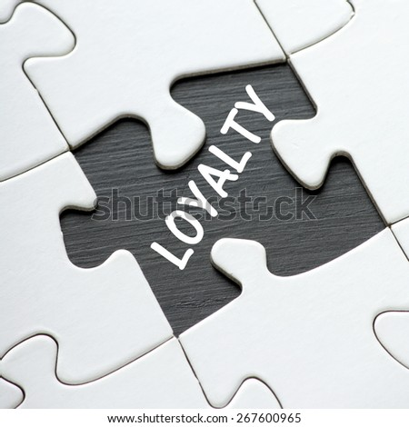 The word LOYALTY revealed on a blackboard by a missing jigsaw puzzle piece - stock photo