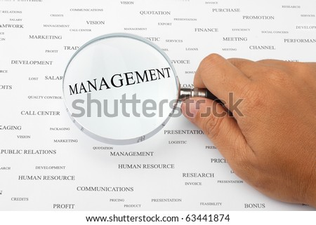 The word MANAGEMENT is magnified. - stock photo