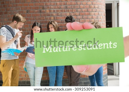 The word mature students and hand showing card against happy students standing and reading - stock photo