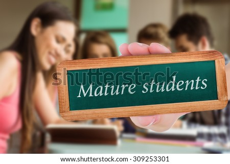 The word mature students and hand showing chalkboard against smiling friends sitting studying and using tablet pc - stock photo