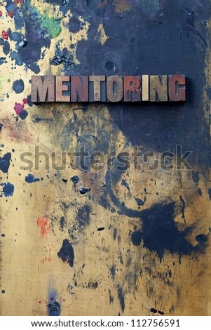The word Mentoring written in antique letterpress printing blocks. - stock photo