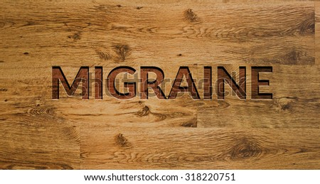 The word MIGRAINE Engraved in Wooden Background. - stock photo