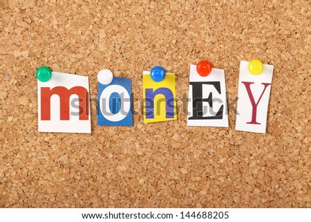 The word Money in cut out magazine letters pinned to a cork notice board