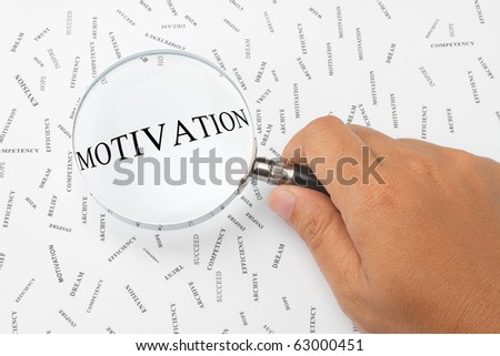 The word, MOTIVATION is magnified. - stock photo