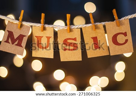 The word MUSIC printed on clothespin clipped cards in front of defocused glowing lights. - stock photo