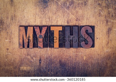 """The word """"Myths"""" written in dirty vintage letterpress type on a aged wooden background. - stock photo"""