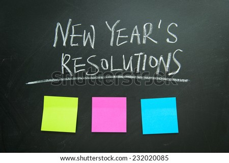 The word New Year's resolution written on the blackboard with blank notes - stock photo