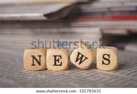 the word news on cubes on a newspaper - stock photo