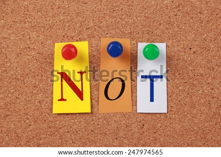The word Not in cut out magazine letters pinned to a cork board. - stock photo