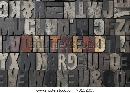 The word On Trend written out in old letterpress blocks. - stock photo