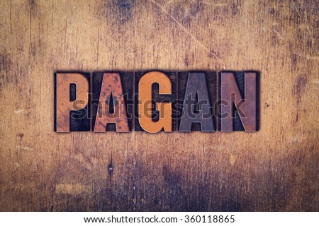 "The word ""Pagan"" written in dirty vintage letterpress type on a aged wooden background. - stock photo"