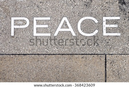 The word Peace in white letters is etched into paving stones.