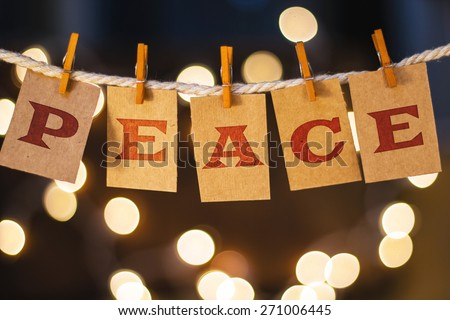 The word PEACE printed on clothespin clipped cards in front of defocused glowing lights. - stock photo