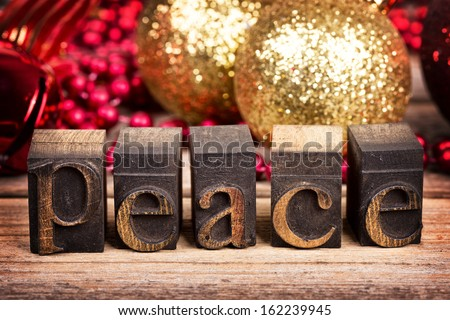 The word PEACE written with vintage wood printer blocks. Christmas message over old wood with traditional tree decorations behind. - stock photo