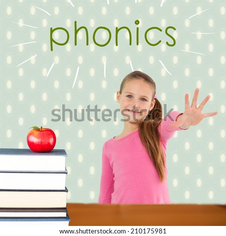 The word phonics and cute girl with hand out against red apple on pile of books - stock photo