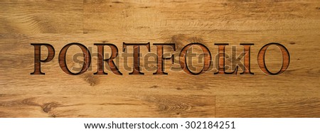 The word PORTFOLIO engraved in wooden background. - stock photo
