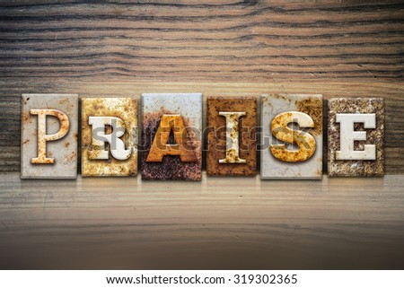"The word ""PRAISE"" written in rusty metal letterpress type sitting on a wooden ledge background. - stock photo"
