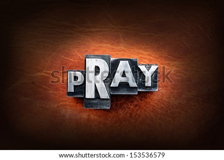 The word pray made from vintage lead letterpress type on a leather background. - stock photo