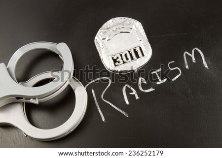 The word RACISM on a chalkboard with a police badge and handcuffs - stock photo