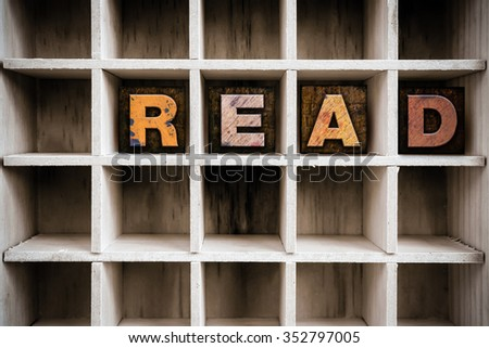 "The word ""READ"" written in vintage ink stained wooden letterpress type in a partitioned printer's drawer. - stock photo"