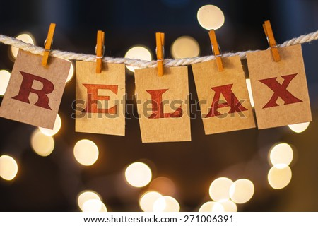 The word RELAX printed on clothespin clipped cards in front of defocused glowing lights. - stock photo