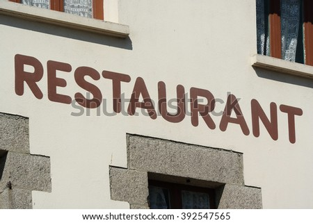 The word Restaurant painted at facade of a building in Brittany, France