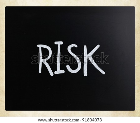 """The word """"Risk"""" handwritten with white chalk on a blackboard - stock photo"""