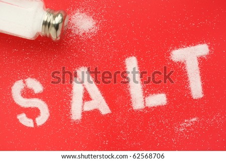 The word SALT in stencil letters using grains of salt from a salt cellar, as a concept for healthy eating or cooking ingredients - stock photo