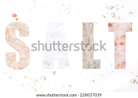 The word salt with mix of four kind of salts over white - stock photo