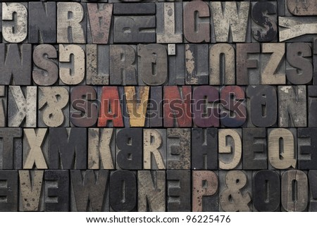 The word Savings written in antique letterpress printing blocks. - stock photo