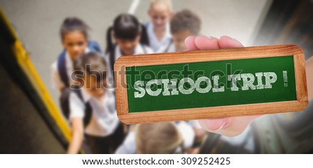 The word school trip! and hand showing chalkboard against cute schoolchildren getting on school bus - stock photo