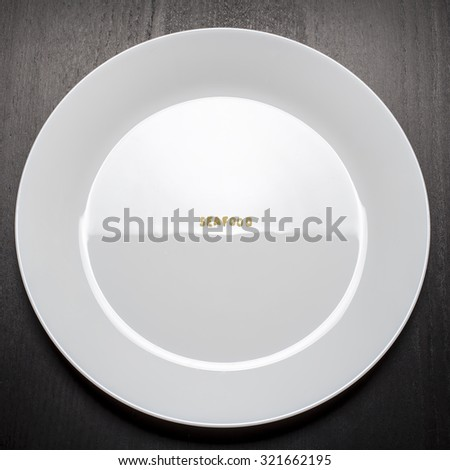 """The word """"seafood"""" is made up of pasta letters on white empty plate, standing on a black table, the incident light creates the illusion of the water surface with waves - stock photo"""