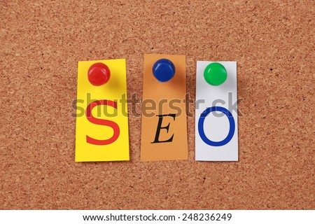 The word search engine optimization in cut out magazine letters pinned to a cork board. - stock photo