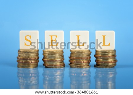 The word Sell on stacked coins, finance conceptual
